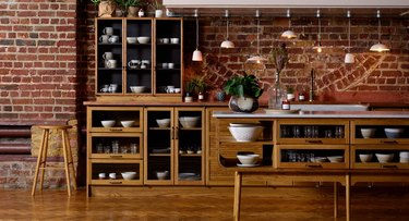 kitchen space with wood cabinets and brick wall