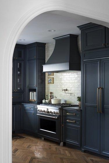 Dark navy blue kitchen color idea with white subway tile backsplash and brass hardware