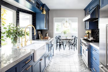 Navy blue kitchen color idea with gold hardware and cement tile floor