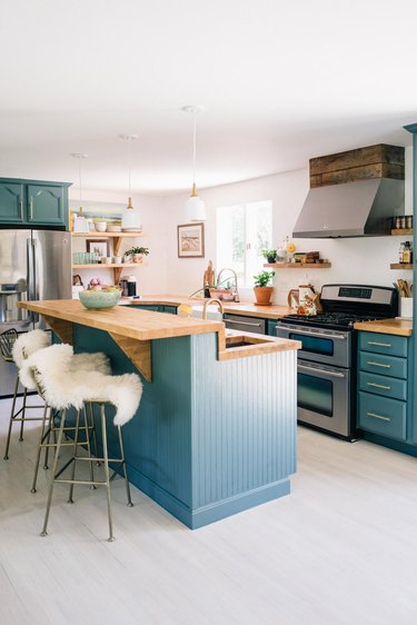 Teal kitchen idea with light wood countertops and bohemian decor