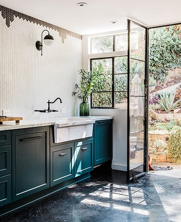 Teal kitchen idea with black and white tile wall and farmhouse sink