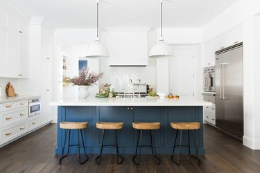 White and navy blue kitchen color idea with navy blue island and wood barstools
