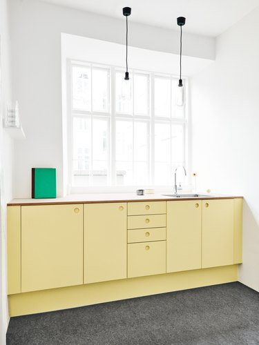 Soft yellow kitchen color idea with lower cabinets in yellow and bright white walls