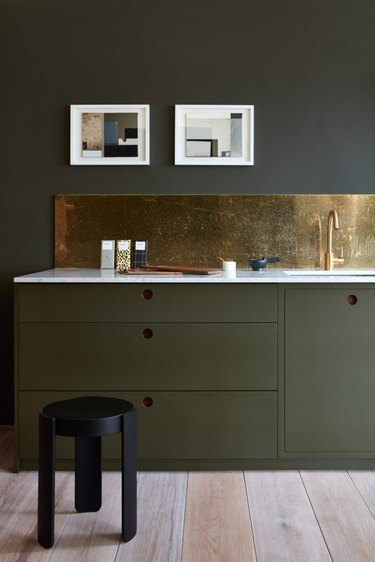 olive green kitchen color idea with gold backsplash and white countertop