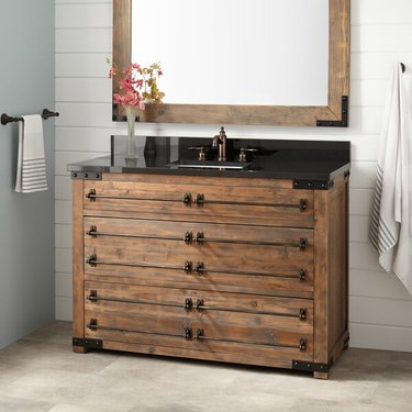 bathroom with wood vanity with black countertop