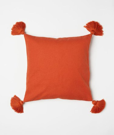 orange accent pillow with fringe tassels from H&M