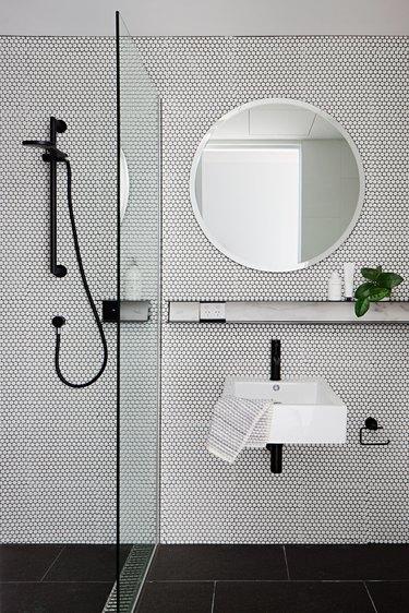 Monochrome utilitarian bathroom with beehive tiles