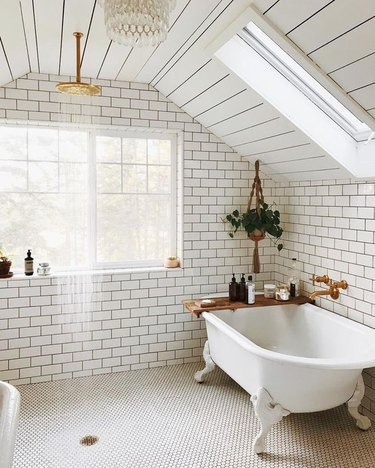 simple white boho bathroom with open shower and hanging botanicals