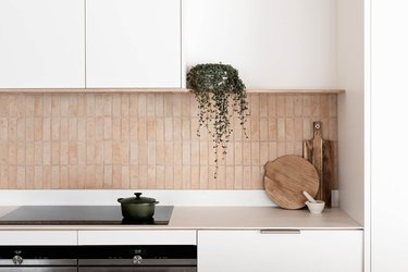white kitchen with exposed vertical terra cotta brick backsplash