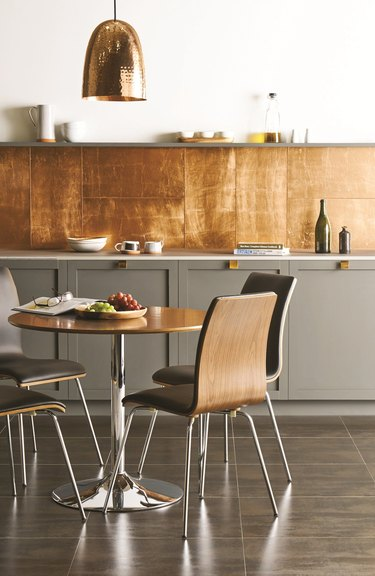gray kitchen with copper backsplash and bell-shaped pendant light