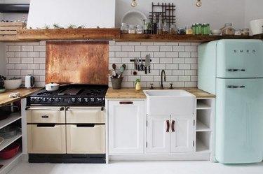 white industrial kitchen with copper backsplash