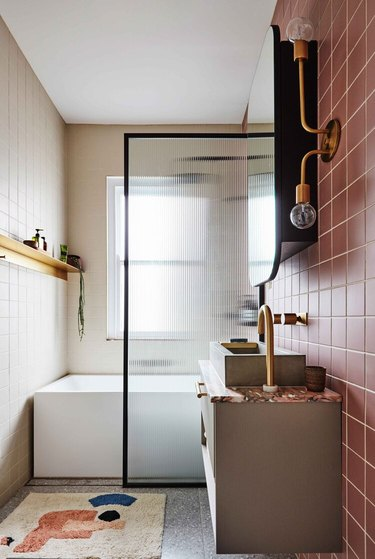 small shower idea with pink tiles and fluted glass screen