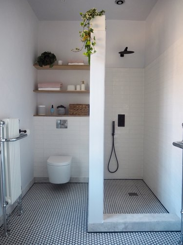 white boho bathroom with small shower and wall divider