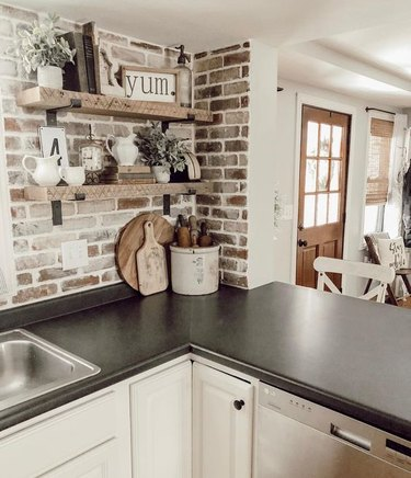 whitewashed brick backsplash with black countertop and white cabinets