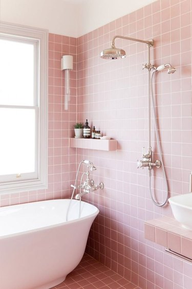 small shower idea with pink wall and floor tile and freestanding tub