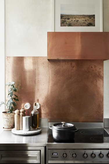 simple kitchen with copper backsplash and cooker hood