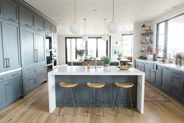 White waterfall countertop in blue kitchen by Studio McGee