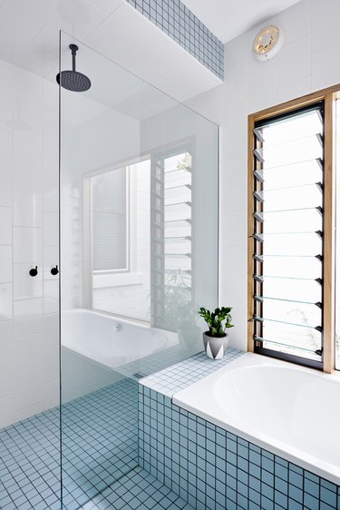 small shower idea with glass divider and blue tile flooring and tub surround