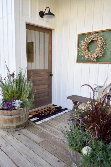 Farmhouse front door idea with flea market decor and potted plants