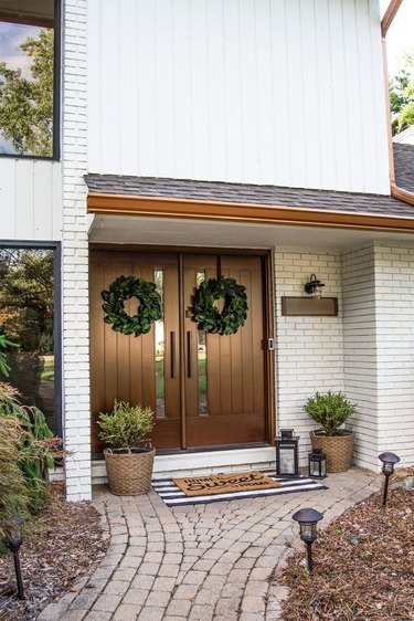 Farmhouse front door idea in a dark wood finish with white brick and green wreaths