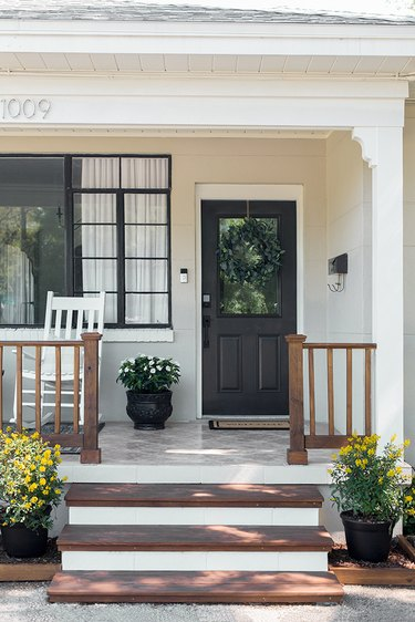 Farmhouse front door idea in black with white exterior and potted plants