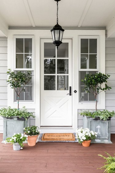 Farmhouse front door idea in white with pendant light lantern and greenery