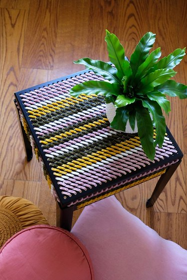 IKEA black perforated table decorated with colorful yarn
