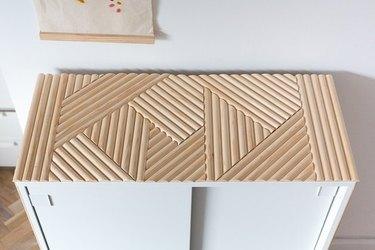 IKEA shoe cabinet with wood dowel details in bedroom.