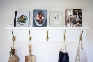 Marry the IKEA Mosslanda picture ledge with Kampig wall hooks to create a gorgeous wall organizer.