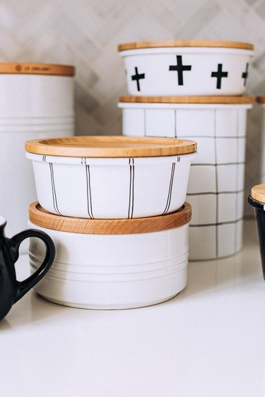 Black and white painted glass jars with wood tops.