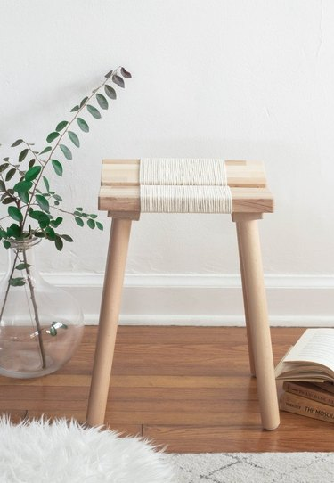 IKEA wood stool with rope details next to glass vase with greenery.
