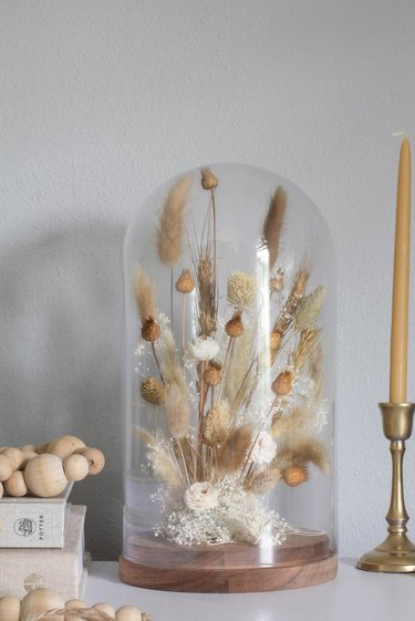Glass cloche with a dried floral design in neutral colors.