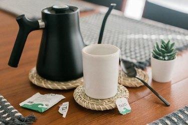 IKEA baskets coasters on coffee table with black coffee pot.
