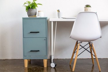 Blue painted filing cabinet next to white desk and modern chair.
