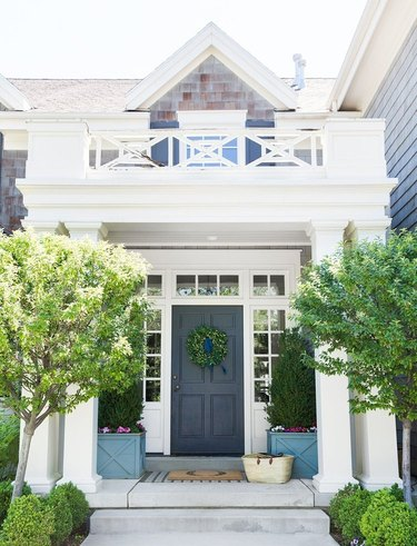 Farmhouse front door idea in navy with boxwood wreath and topiaries