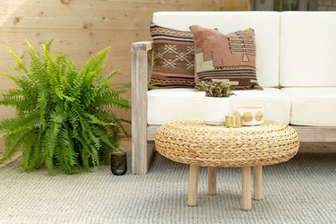 IKEA floor pad used as a coffee table on patio with couch and plant.