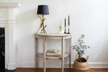 Bleached wood console table with black lamp and candles on top next to a basket with plant inside.