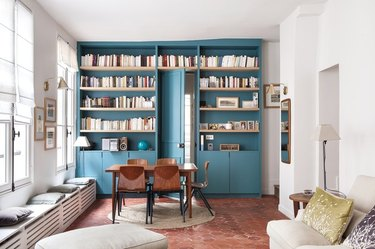 narrow apartment with terra-cotta floors and built-in bookcase