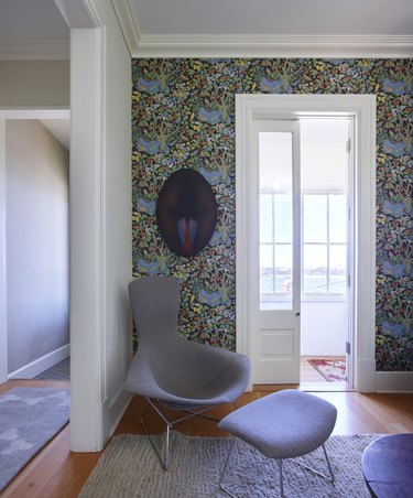 Hallway and seating area with patterned wall paper and modern chair