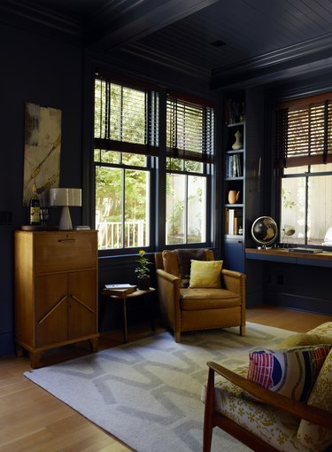 Dark blue painted study with vintage wood furniture and wood floors