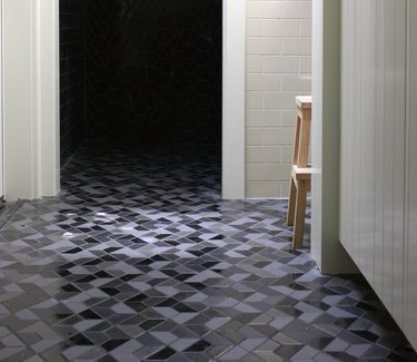Multicolored geometric tile floor and white subway tile wall