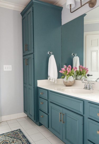 Teal bathroom cabinets with white countertop and white tile floor