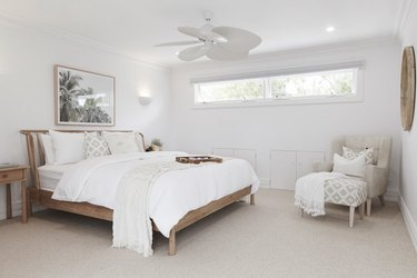 all white bohemian bedroom with wood bed and mirror