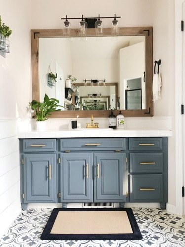 Blue gray cabinets in farmhouse bathroom with cement tile and wood framed mirror