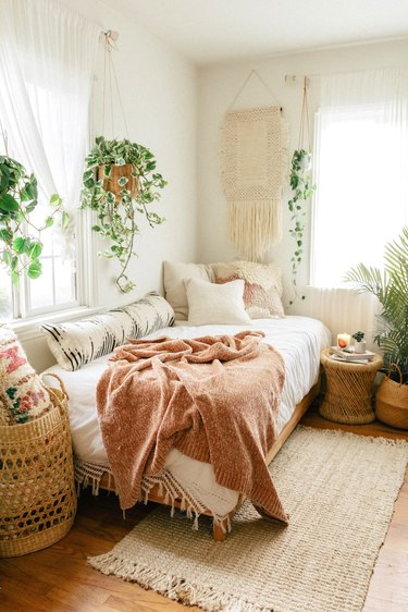 white bohemian bedroom with macrame wall hanging and plants