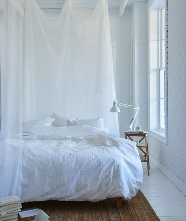 bedroom space with white sheets and hardwood floor