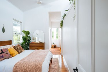 white bohemian bedroom with potted plants and coral accents
