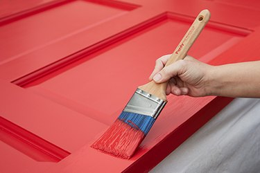 Painting a door with a paintbrush.