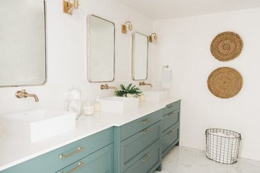 Pine bathroom cabinets with white walls and baskets on wall