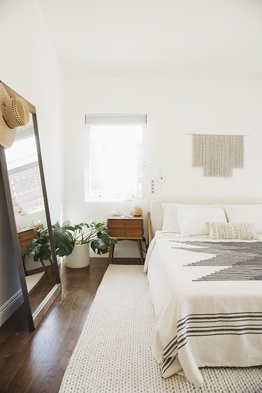 white bohemian bedroom with wall hanging and boho throw.